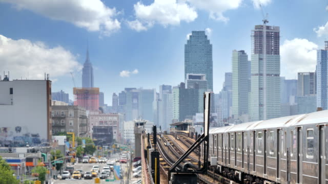 view of manhattan skyline as seen from elevated subway platform in queens - viale video stock e b–roll