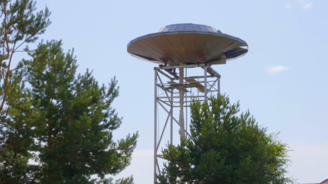 View of metal UFO on supports in forest with trees video