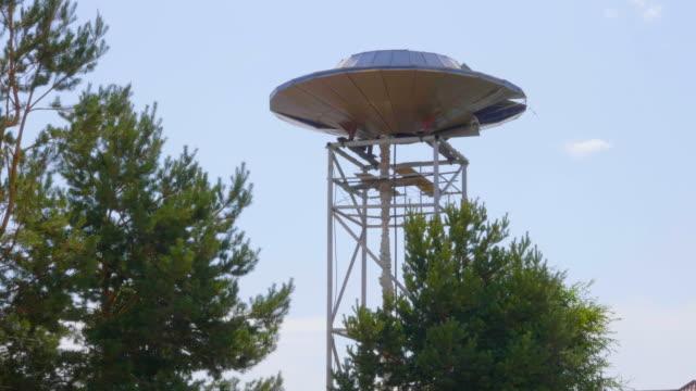 metal ufo görünümünü destekler orman ağaçları ile - zeplin stok videoları ve detay görüntü çekimi