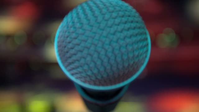 View of microphone on stage facing empty auditorium.  Colorful spotlights video