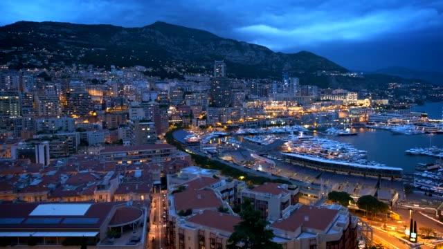 View of Monaco in the night View of Monaco Monte Carlo harbour and city skyline in the evening. Monaco Port night view with fast moving clouds. Horizontal camera pan monte carlo stock videos & royalty-free footage