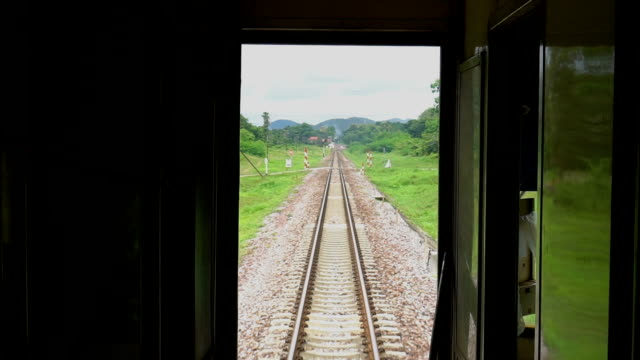 View of passing landscape while traveling by train View of passing landscape while traveling by train. Chiang Mai, Thailand railroad track stock videos & royalty-free footage