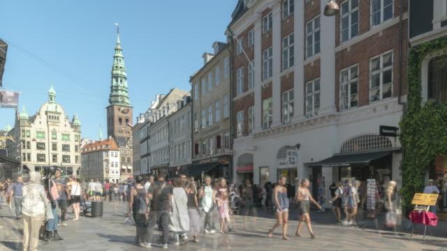 tl utsikt över fotgängare och resenär runt en av shopping- och marknadsgatan nära stork fountain korsningsväg på en av marknadsgatorna på ett centralt torg i köpenhamn, danmark, ett av norden på sommaren. - dansk kultur bildbanksvideor och videomaterial från bakom kulisserna