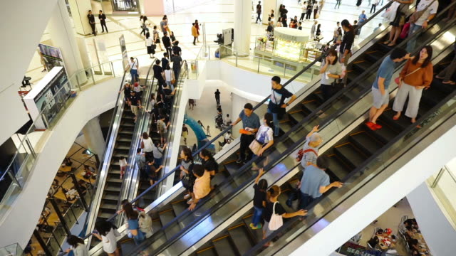 view of people taking white escalators in shopping mall in bangkok - escalator video stock e b–roll