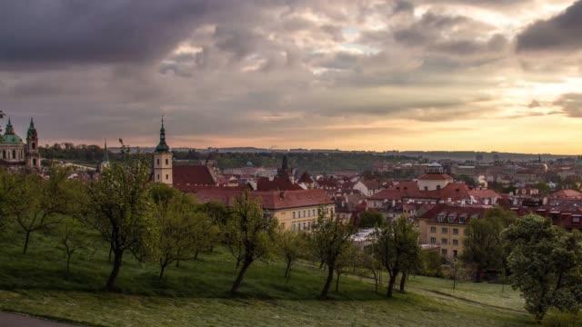vidéos et rushes de vue des toits de ville vieux prague, l'église saint-nicolas, arbres et bâtiments comme vu du parc avec des arbres jeunes, timelapse, printemps diurne nuageux météo république tchèque - saint nicolas