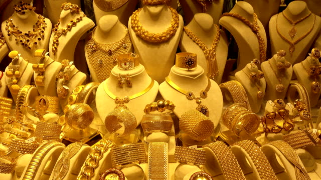 4K view of precious gold necklaces, earrings and bracelets on rotating stands.