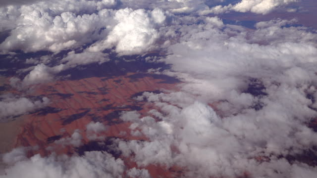 SLOW MOTION: View of red arid sandy landscape and numerous puffy white clouds video
