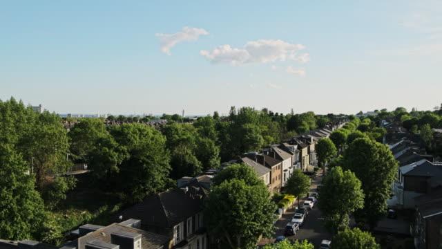 vidéos et rushes de vue de logement résidentiel en terrasse dans le centre de londres, royaume-uni avec des arbres luxuriants dans l'environnement - tir panoramique à angle élevé - nord