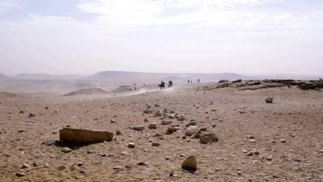 View of riders on horses who running fast in the desert, under the hot sun, in Egypt.