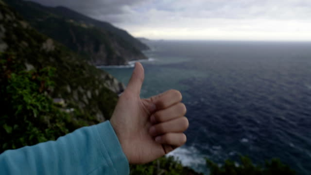 View of rocks and the sea at Cinque Terre in Italy, male hand showing thumbs up