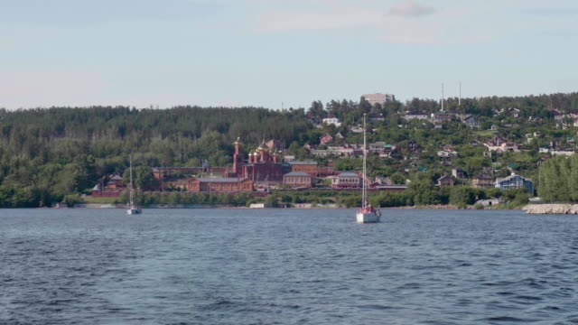 View of sailing yachts in river and green coast with red buildings of Voskresensky monastery video