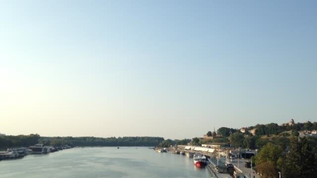 view of sava river bank in belgrade.  kalemegdan fortress, one of the symbol of the serbian capital city, can be seen on the right, while boats are passing by on the river - белград стоковые видео и кадры b-roll