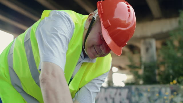 View of senior railroader in uniform smiling during work process at railway video