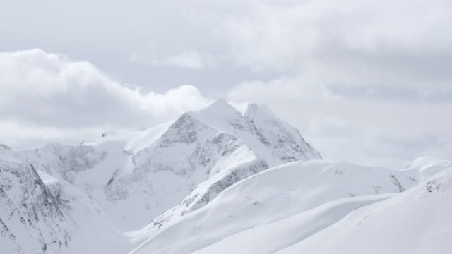 View of snow capped mountains on a cloudy winter day video