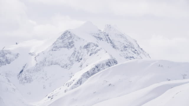 View of snow capped mountains on a misty winter day