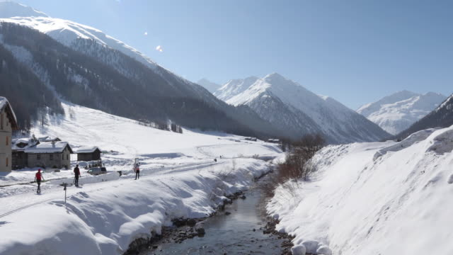 view of snowy mountains and mountain creek, distant skiers - livigno video stock e b–roll