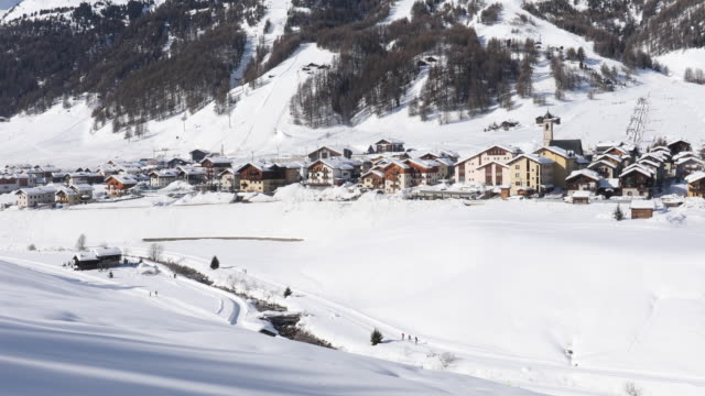 view of snowy mountains and village below - livigno video stock e b–roll