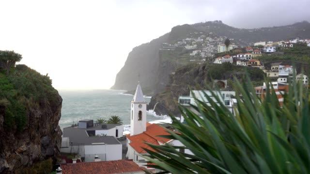 vídeos de stock e filmes b-roll de view of são sebastião church with cape girão, in câmara de lobos, madeira - ilha da madeira