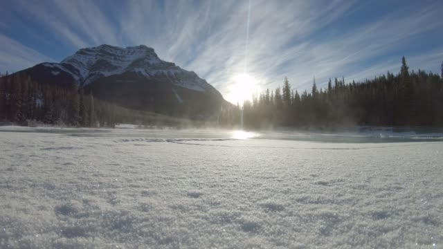 View of steam rising from icy pond, in mountains