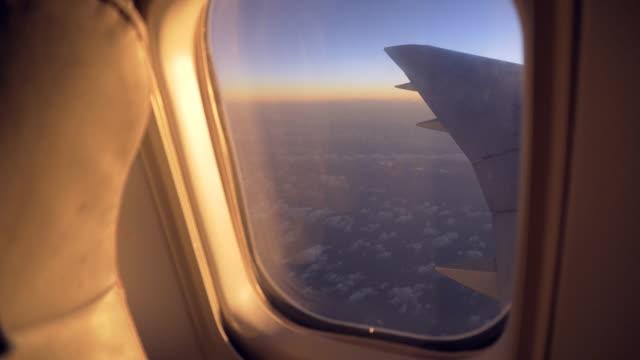 View of sunrise through airplanes window during flight video