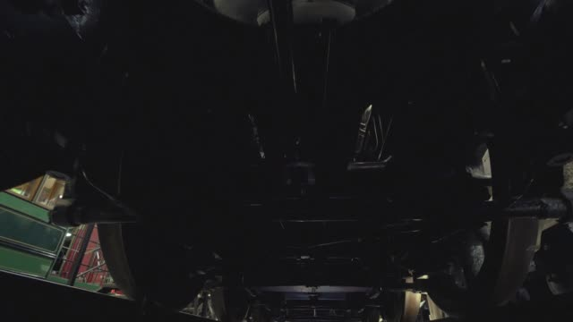 View of the bottom of train, a walk under the train. Steadicam shot