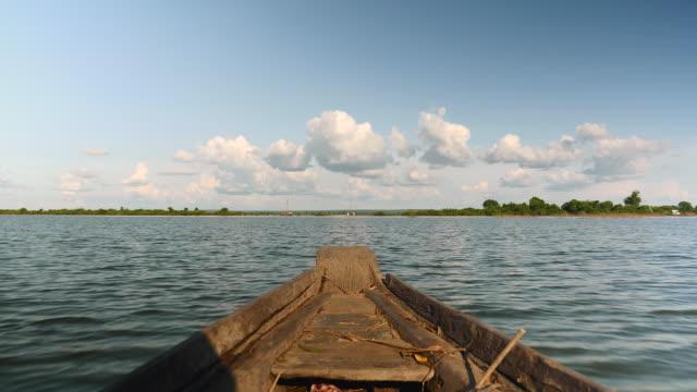açık bir günde gölüzerinde bir yolculuk sırasında küçük bir motorbot yay görünümü - kamboçya stok videoları ve detay görüntü çekimi