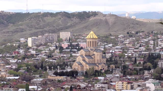 View of the Cathedral of Sameba, Tbilisi and the mountains, some tree branches in the foreground