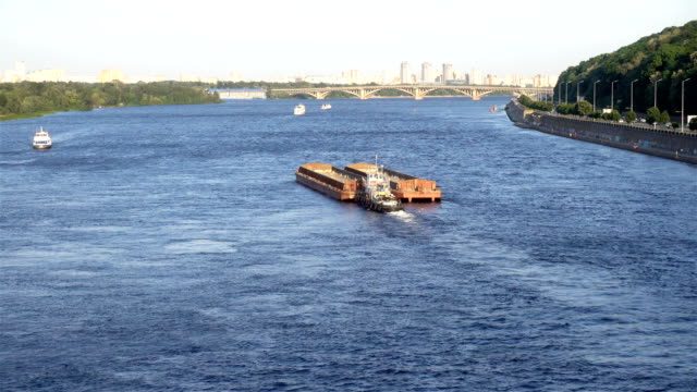 4k view of the dnieper with barge and city skyline. - chiatta video stock e b–roll