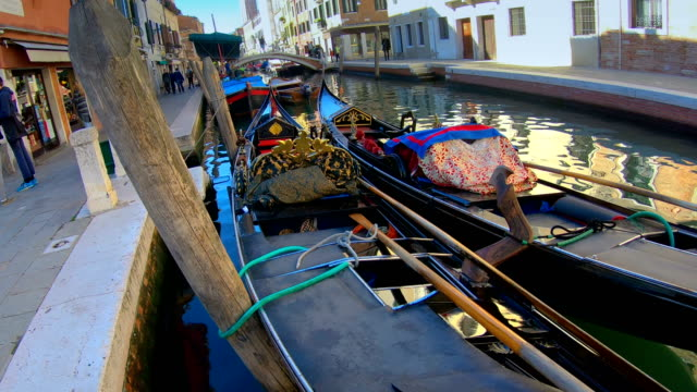 View of the gondolas in the side of the canal in Venice Italy video