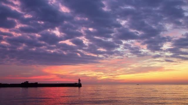 utsikt över fyren vid gryningen stående på kusten - pink sunrise bildbanksvideor och videomaterial från bakom kulisserna