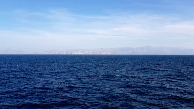 vídeos de stock e filmes b-roll de view of the ocean and clouds in the sky. mountains and ocean on the horizon.blue sky with clouds in sunny weather over the ocean. - circular economy