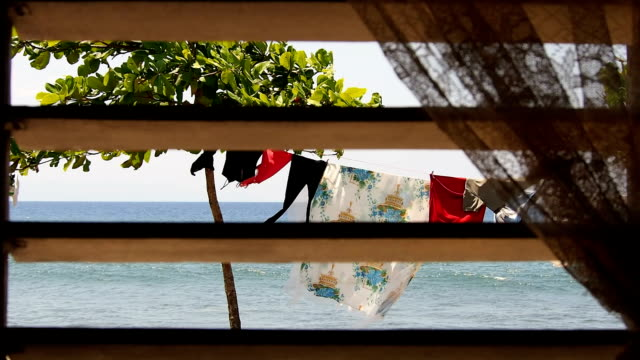 View of the ocean and drying rack through a window with colonial style sun shutter, Cuba video