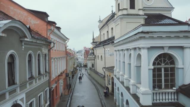 blick auf die altstadt von vilnius, touristen zu fuß durch die engen gassen - litauen stock-videos und b-roll-filmmaterial