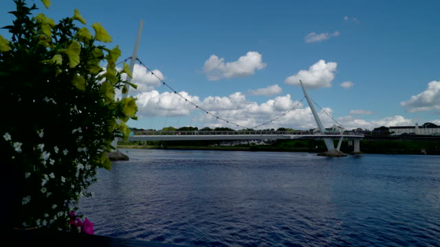 view of the peace bridge found in the city of londonderry - графство дерри стоковые видео и кадры b-roll
