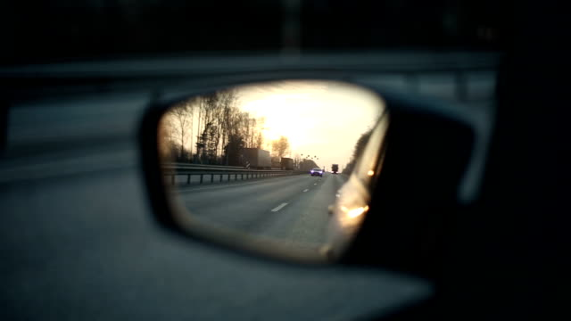 View of the road in the rearview mirror at sunset View of the road in the rearview mirror at sunset rear view mirror stock videos & royalty-free footage