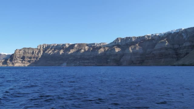 View of the Santorini cliff from a boat On the top of that cliff you can find the city of Firá, the biggest city of the island of Santorini, Greece, Europe aegean islands stock videos & royalty-free footage