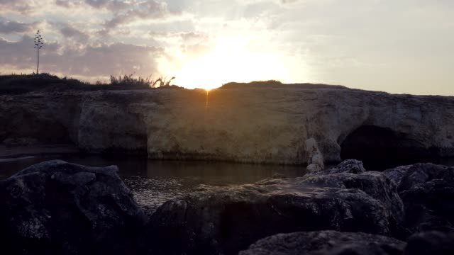 View of the sun rising from rocks at the Cirica Bay, Italy, 4K