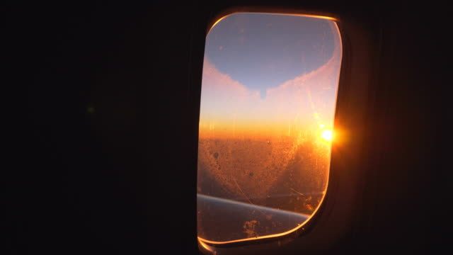 View of the sunrise from airplanes window during the flight video