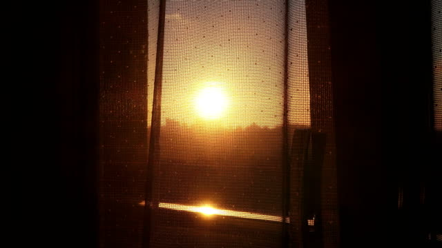 View of the sunset from the window  through transparent curtain