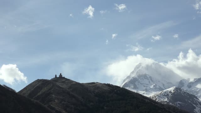 View of the temple of the Holy Trinity Gergeti on the background of floating clouds and Mount Kazbek. Georgia, Caucasus.