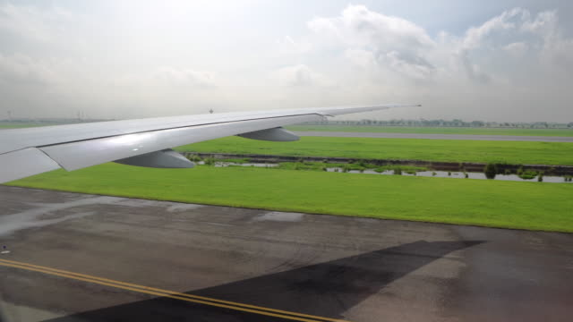 view of the wing of the aircraft from the window. aviation and passenger transportation view of the wing of the aircraft from the window. aviation and passenger transportation. airfield stock videos & royalty-free footage
