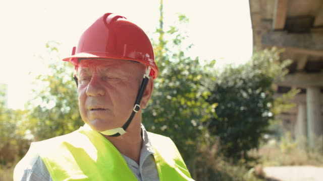 View of thoughtful senior engineer looking around during a work in summer day video