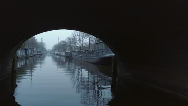utsikt över lugn kanal med båtar under kalla årstiden - drone amsterdam bildbanksvideor och videomaterial från bakom kulisserna