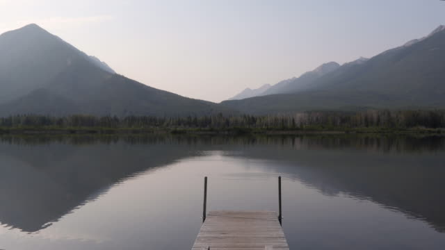 view of tranquil lake and distant mountains - molo video stock e b–roll