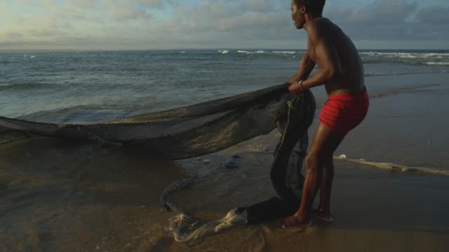浅い波でセーヌネットを働く2人の生存漁師の4kビュー、モザンビーク - 漁師 外人点の映像素材/bロール