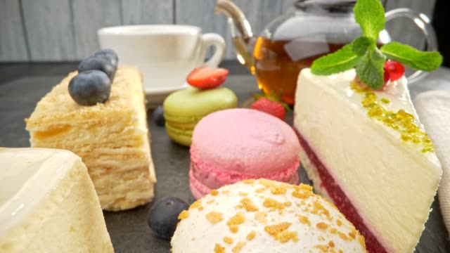vídeos de stock e filmes b-roll de view of various sweets, including napoleon, cheesecake and other cakes, berries and teapot. slider shot, 4k - bolos
