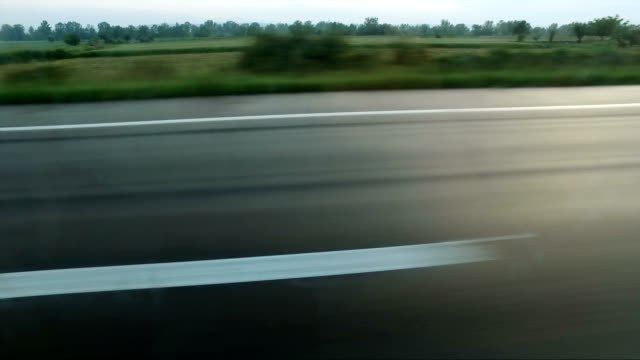 View of wet asphalt and dividing lines on highway during sunset from car in motion video