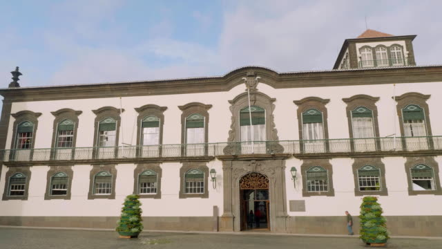 View of white building with windows and doors in Funshal video