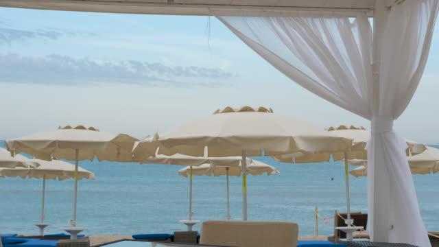 blick auf weiße sonnenschirme am strand. - sonnenschirm stock-videos und b-roll-filmmaterial