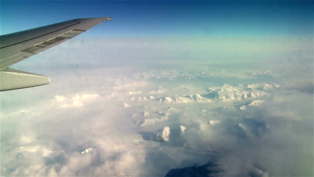 View of wing in blue sky and snow-capped mountains out from flying airplane. video
